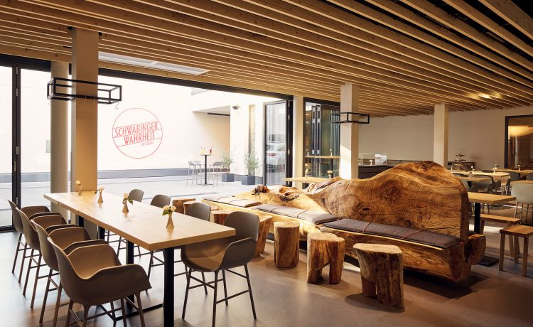 Seating area in the interior of the Schwabinger Wahrheit with stylish solid wood bench and solid wood tables.