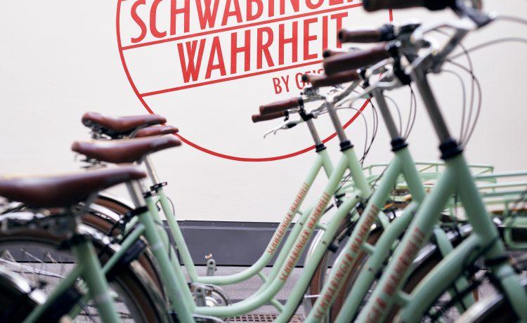 Detailed view of City-Bikes with Schwabinger Wahrheit logo in the background.