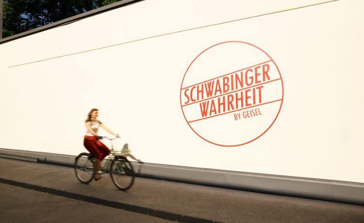 Cycling young woman with red trousers in front of a white wall with Schwabinger Wahrheit logo.