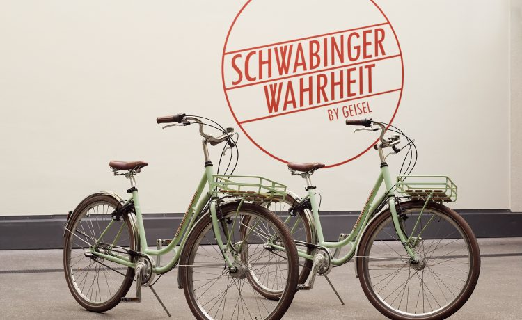 Two green city bikes in front of a wall with logo of the Schwabinger Wahrheit.