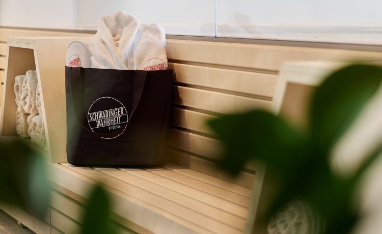 Bench with spa accessories in black carrying bag and white Schwabinger Wahrheit logo.