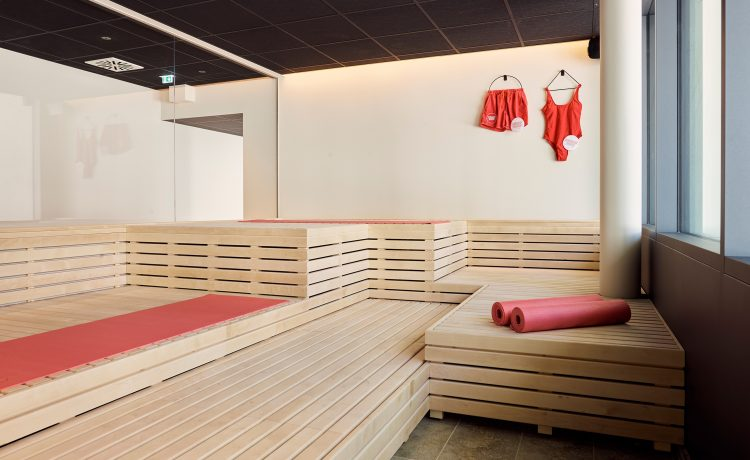 Sauna area with light wood and red bathing suits on the wall.