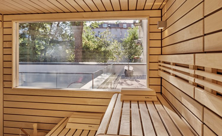 Interior view of the sauna area with a view of the outside through a large pane.