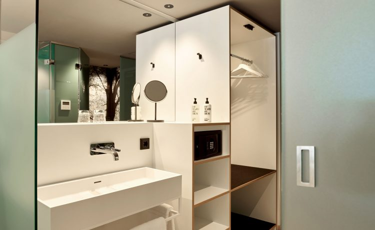 White-washed bathroom with large wall mirror Schwabinger Wahrheit.