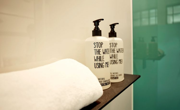 Two white shampoo bottles with black writing on the shower tray in the Schwabinger Wahrheit.