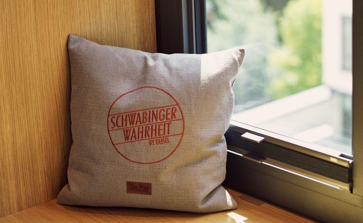 Cushion with embroidered Schwabinger Wahrheit logo.