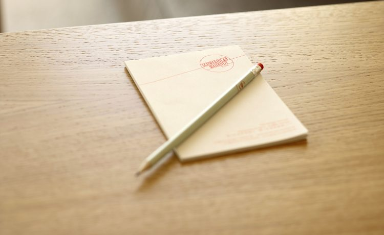 Notepad with pencil on wooden bedside table in the Schwabinger Wahrheit.