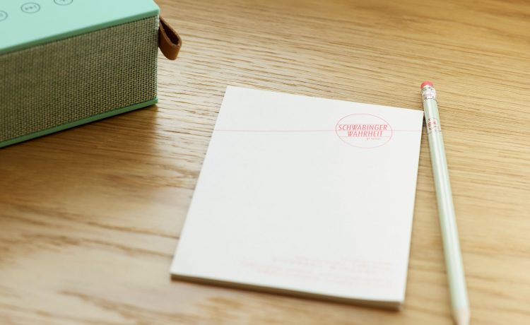 Notepad with pencil, printed with the Schwabinger Wahrheit logo.