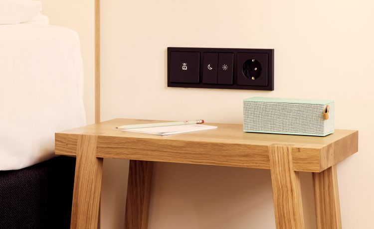 Bedside table with writing pad and loudspeaker box.