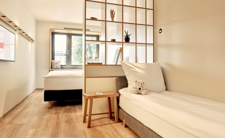 Room with sofa bed, room divider and double bed in the background.