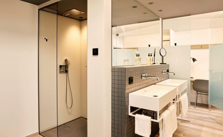 Large bathroom with double washbasin and standing shower in suite 35.