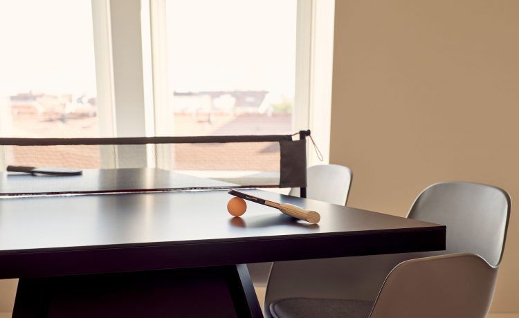 Table tennis table with bat and orange ball in suite 63.