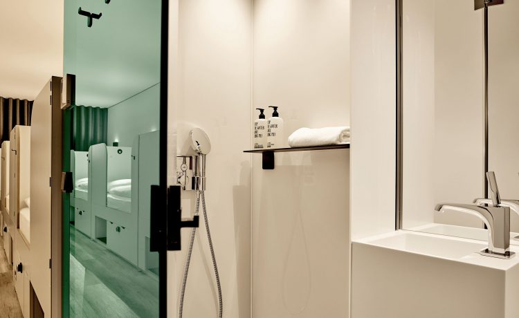 View into the bathroom with standing shower and washbasin of the team room.